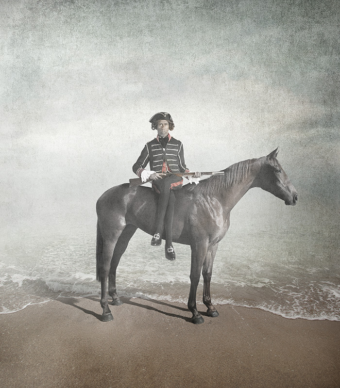 An Indigenous man in period attire sits side saddle on a horse