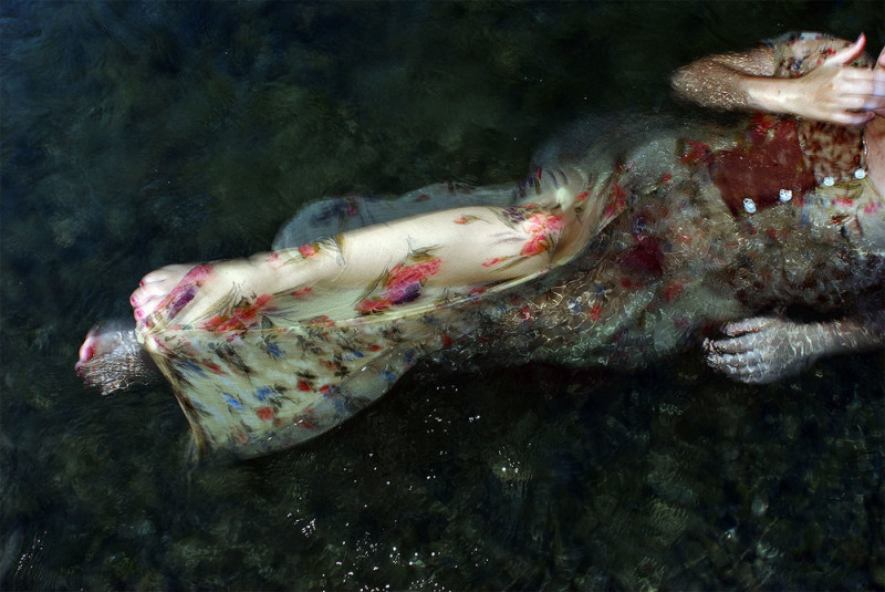 A woman in a floral dress floats in water